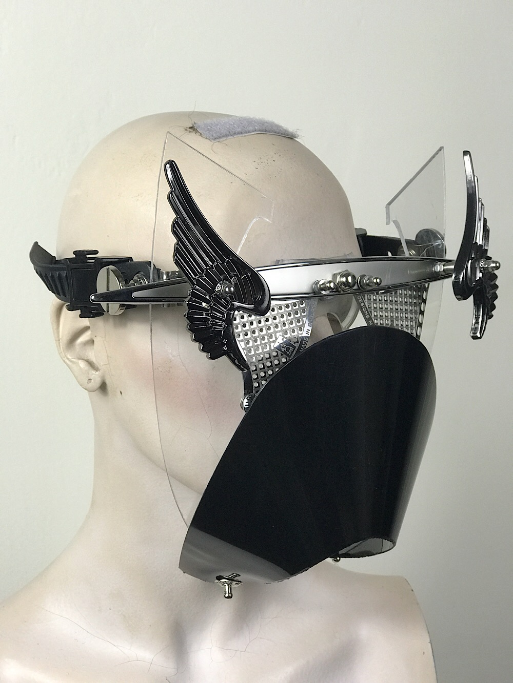 Metal mask with wings perforated metal ocular lenses and muzzle
